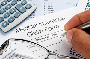 Medical insurance claim form with pen glasses calculator and writing hand